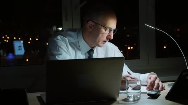 Thoughtful business man making note in notebook while last work in dark office