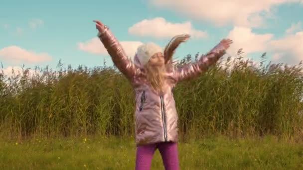 Šťastná dívka hravý tanec a skákání venku s rákosím