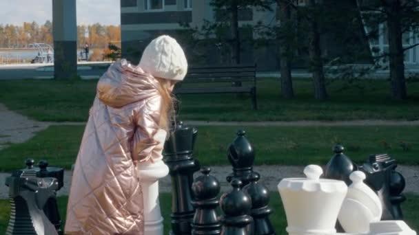 S úsměvem preteen girl stěhování šachové královny na palubě a vítězná hra