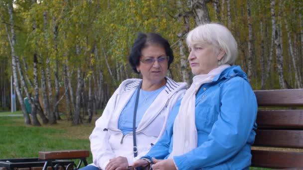 Dvě starší ženy sedí na lavičce v parku