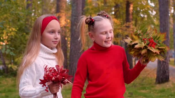 Portrait of cheerful girls holding bouquets with autumn leaves and rowan