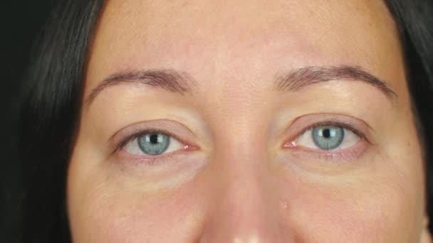Női arc a nyitott szemmel kacsintás, és vizsgálja a kamera közelről