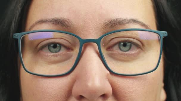 Zblízka usmívající se žena v brýlích s otevřenýma očima blikající a při pohledu do kamery