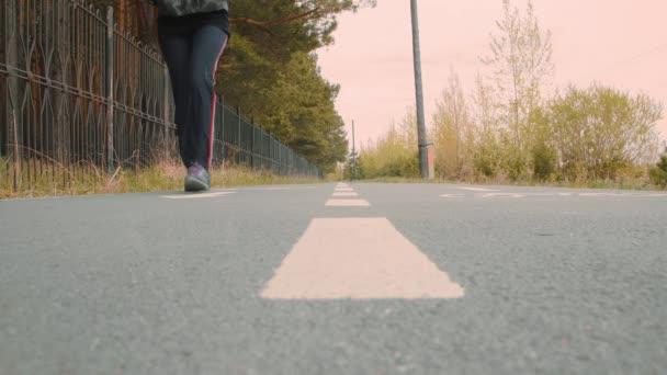 Nohy pěší chůze po asfaltové cestě za plot v parku na podzimní den