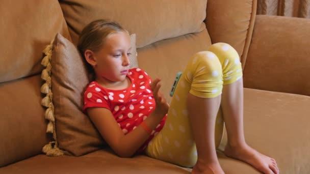 Dospívající dívka sedí na pohovce v útulné místnosti interiéru pomocí mobilního telefonu