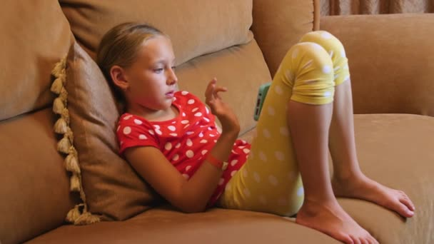 Dospívající dívka sedí na gauči, pomocí mobilního telefonu v interiéru obývacího pokoje
