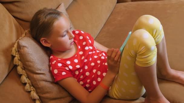 Mladá dívka sedí na gauči a procházení mobilního telefonu v útulném obývacím pokoji