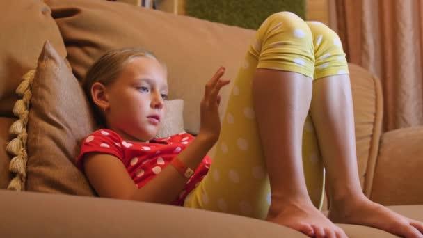Dospívající dívka na gauč a surfování internetu na mobilní telefon v pokoji, nízký úhel