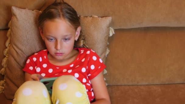 Mladá dívka sedí na pohovce a chatování v sociálních médiích pomocí mobilního telefonu v pokoji