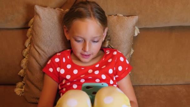 Usmívající se dívka dospívající pomocí mobilního telefonu na pohovku vnitřní obývací pokoj