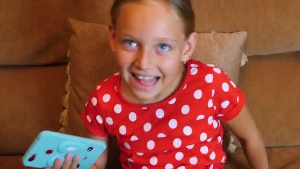 Veselá dospívající dívka usmívá a pomocí smartphone na pohovku v domácím místnosti