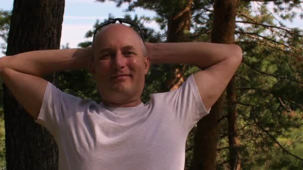 Happy bald man in white t-shirt relaxing in summer forest or park