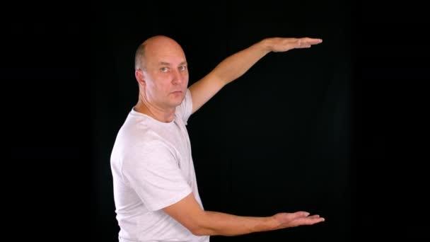 muž ukazuje něco velkého a něco malého mezi rukama