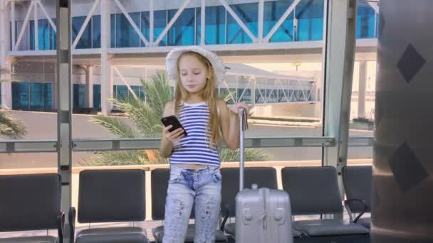 Mladá dívka s mobilním telefonem a kufr čekající v odletové hale letiště