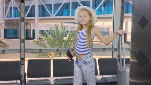 Dívka s cestovní kufr volání mobilním telefonem v odletové hale letiště