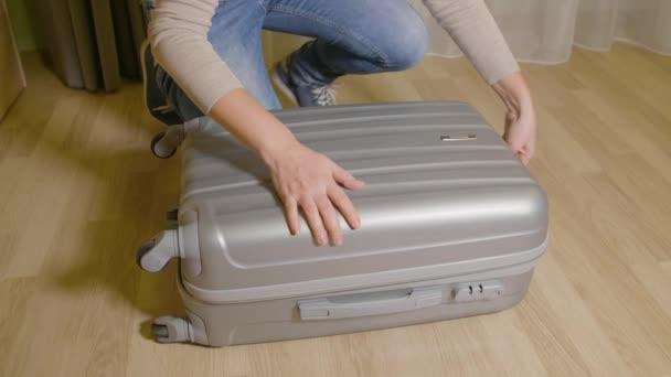 Dívka, zavírání zip zapínání na cestovní kufr. Žena tahání zip kufr