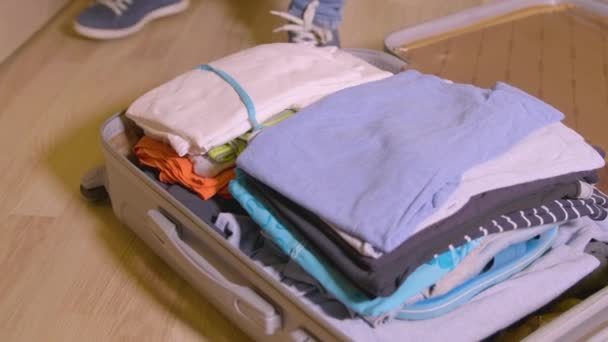 Žena uvedení věci a oblečení v kufru cestování na podlaze v domácím místnosti