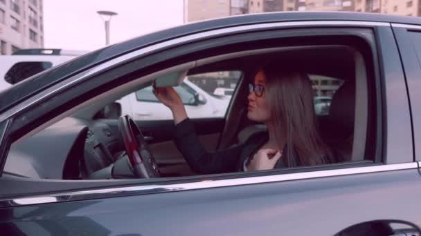 Auto vypadá dáma v zrcadle zadní pohled pro kontrolu make-up v autě. Žena v zaparkovaném autě