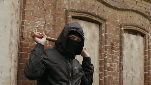 Aggressiver Hooligan in Maske und Kapuze mit Baseballschläger in der Nähe eines Gebäudes auf der Straße. halbe Länge des Banditen, der im Freien ein Verbrechen begeht, Handschuss