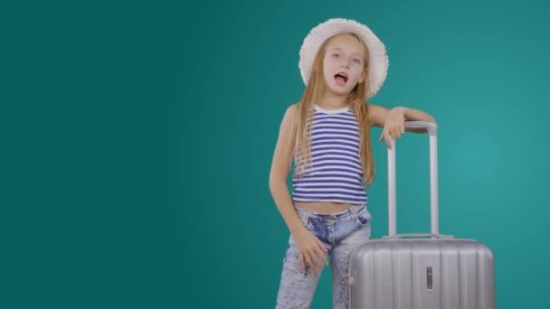 Veselá dívka cestovní blogger s kufrem zve na výlet na zeleném pozadí