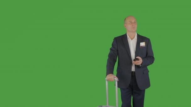 Obchodní muž s cestovní kufr drží mobilní telefon na zeleném pozadí