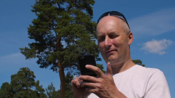 Caucasian man browsing mobile phone on green pine background in summer forest