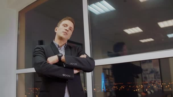 Successful businessman in classical formal suit standing in evening office with hands crossed on chest near window, looking at camera, ready for new projects, challenges.