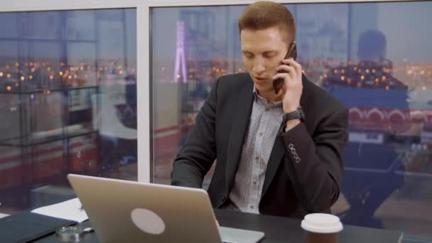 Succssful business man discussing deal by mobile phone at table in business office