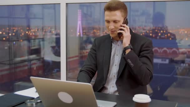 Young business man on window background while mobile conversation at work table