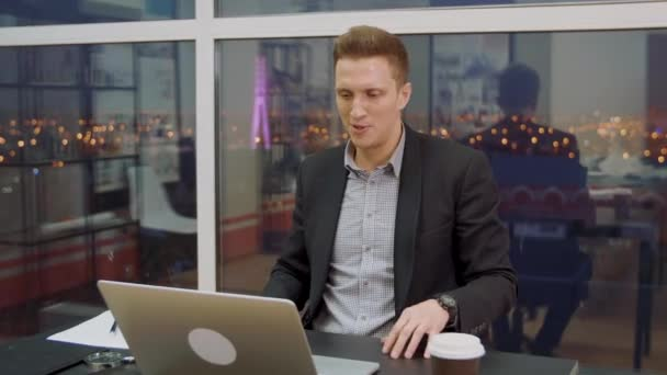 Surprised business man watching shocking news in laptop computer in office