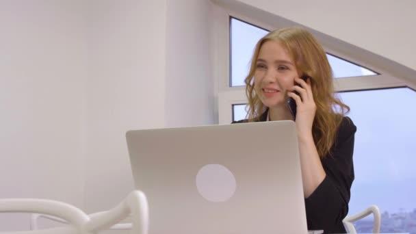 Usmívající se obchodní žena mluví o mobilní telefon při práci na přenosném počítači v kanceláři. Veselá žena podnikatel volání obchodnímu partnerovi smartphone. Prázdné copyspace