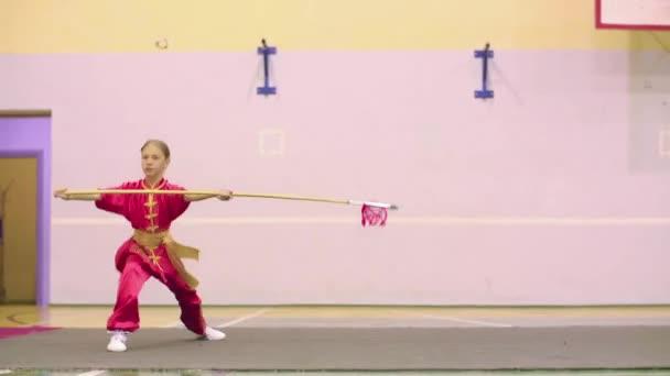 Young girl in red yifu clothes doing qiansho form exercises china kung fu tai chi.