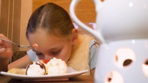 Detailní záběr dospívající dívka jíst zmrzlinu dezert u stolu v restauraci