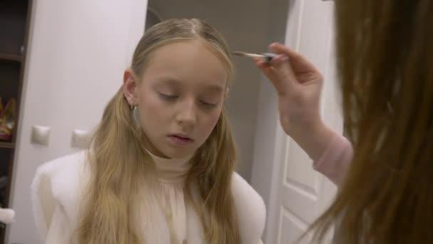 Vizážistka dělá tvoří mladá dívka teenager v kosmetické studio face