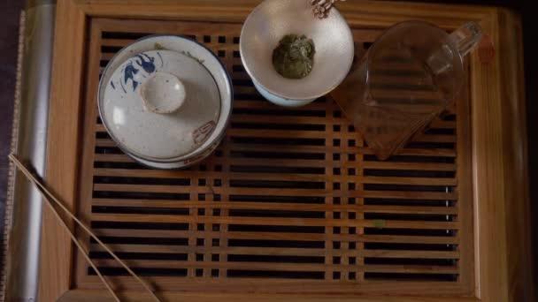 Detailní záběr rukou milovník čaje si vzal šálek zeleného čaje z pohledu shora dřevěný stůl