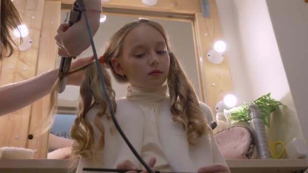 Krásná dívka a curling dlouhé vlasy žehlička na vlasy v kadeřnictví salon nízký úhel
