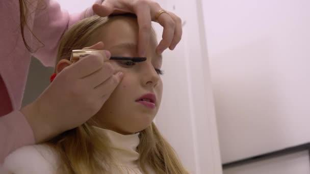 Portrét dospívající dívka při použití řasenky na řasy v make-up studio