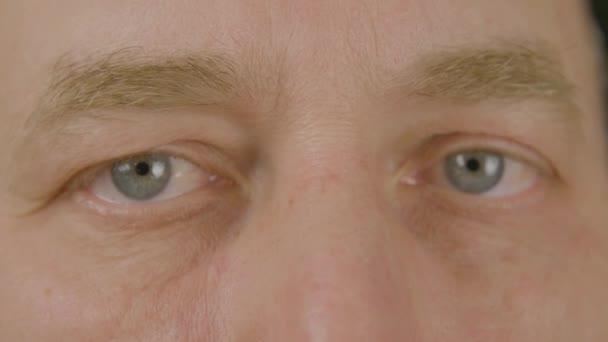 Muž s otevřené oči při pohledu a blikající přední kamera zblízka. Makro mužské oči