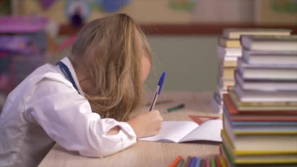 Iskola lány asztalnál írás jegyzetfüzet hossz-szelvény nézetben. Közelkép iskolás lány írásban iskola notebook, és bemutatja remek, mert tanulságok
