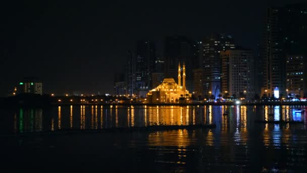 Boat float by sea lagoon in front of mosque illuminated with gold light. Night view of big city. Seashore in megapolis and skyscrapers shine and flickering lights.