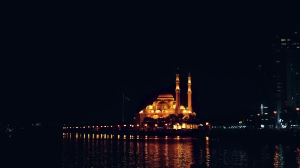 Night view of illuminated with gold light mosque at waterfront. Panning shot evening seashore. Lights of big city.