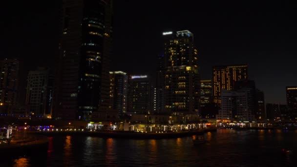 Panoramatický pohled od promenády na noční město a vysoké mrakodrapy v Dubai Marina