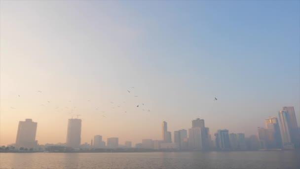 Sharjah, United Arab Emirates - January 18, 2018. Quay at Al Buheirah Corniche near Khalid lake. Foggy morning. Arabian man in thawb. Arab man walks through quay along the sea at foggy morning.