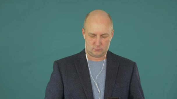 Adult man using smartphone for listening music in headphone