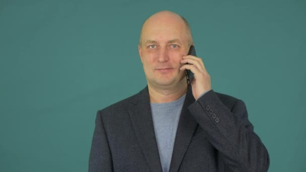 Portrait adult man talking on mobile phone on green background