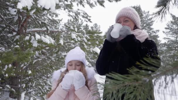 Mother and daughter drinking hot drinks in winter forest.