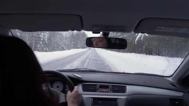 Woman driving a car. Adult woman driving a car slowly and carefully. Winter forest aside the road POV
