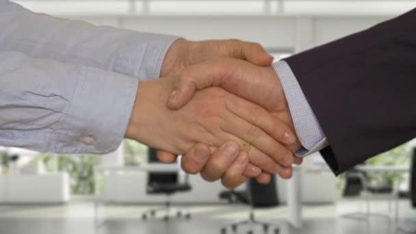 Obchodní handshake se dvěma rukama v moderní kanceláři. Oříznutý pohled podnikatelka a podnikatel potřesení rukou po dohodě
