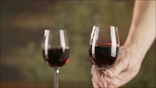Ausgeschnittene Ansicht eines Mannes, der ein Glas Rotwein neben ein anderes Weinglas auf den Tisch stellt, Zeitlupe