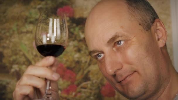 Tvář člověka při pohledu na červené víno ve skle před ochutnávkou zblízka. Portrét muže pít červené víno ze skla
